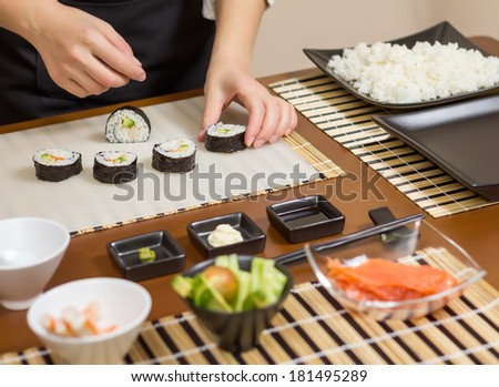 Closeup of woman chef putting japanese sushi rolls with rice, avocado and shrimps on nori seaweed sheet - stock photo
