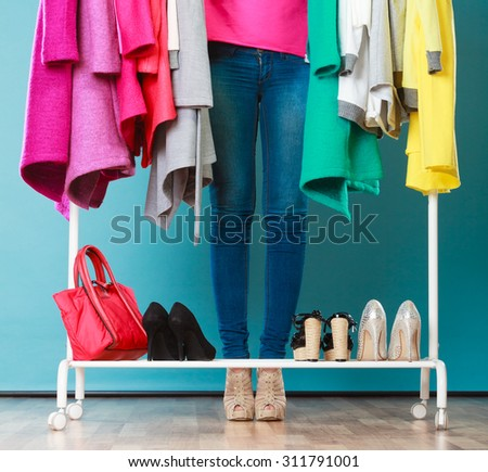 Closeup of woman choosing clothes to wear in wardrobe. Girl customer shopping in mall shop. Fashion clothing sale concept.