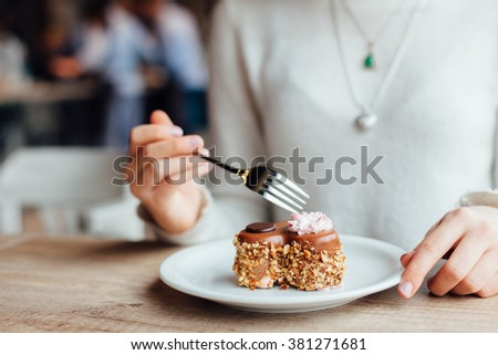 Closeup of woman eating chocolate cake in a cafe - stock photo