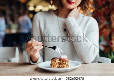 Closeup of woman eating chocolate cake in a cafe