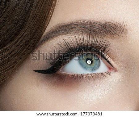 Closeup of woman eye with beautiful makeup with black eyeliner and long eyelashes - stock photo
