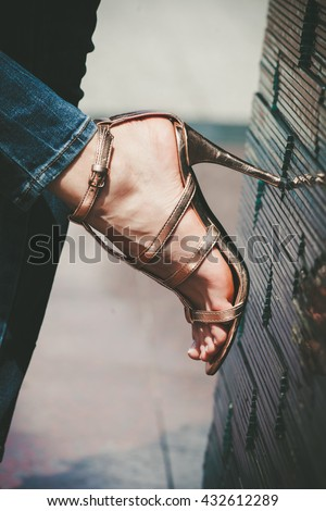 closeup of woman foot in golden high heel sandals lean on tiled wall outdoor shot - stock photo