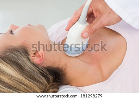 Closeup of woman getting an ultrasound scan on neck by doctor - stock photo