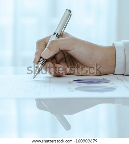 Closeup of woman hand holding pen on document - stock photo