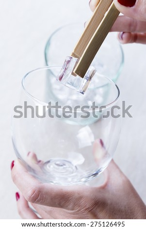 closeup of woman hands adding ice cubes to a balloon glass from an ice bucket with a bamboo ice tongs on a gin tonic preparation session - focus on the ice cube - stock photo