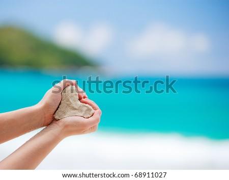 Closeup of woman hands holding white tropical beach form heart shape - stock photo