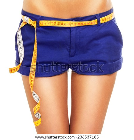 Closeup of woman hips and thighs with thigh gap. Young Caucasian slim woman in blue shorts diet and weight loss concept.  - stock photo