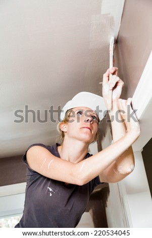 Closeup of Woman Holding Paint Brush and Painting the Ceiling - stock photo