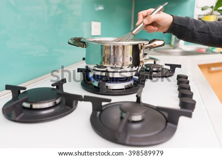closeup of woman  in kitchen  cooking soup on a stove - stock photo