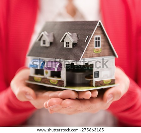 Closeup of woman mortgage consultant holding house model. Concept of new home sale or rent. Shallow depth of field. - stock photo