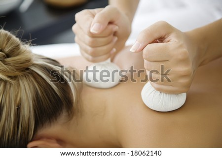closeup of woman receiving massage with herbal balls