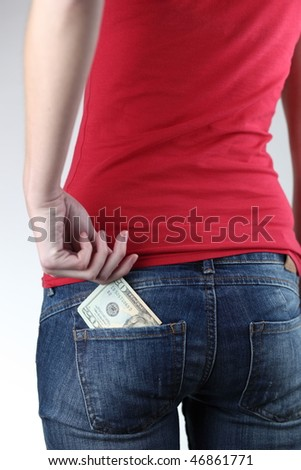 Closeup of woman's bottom with banknotes in the pocket (she is reaching for the money in order to pay for something/she is putting the money in her pocket) - stock photo