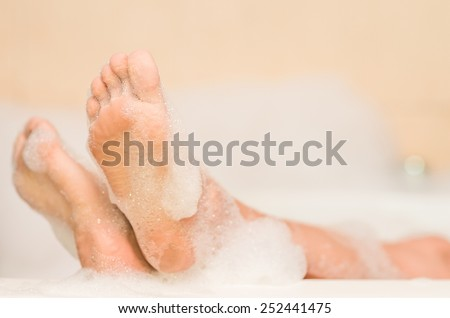 closeup of woman's feet covered with foam bubble bath - stock photo