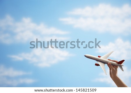 Closeup of woman's hand flying toy plane against cloudy sky - stock photo