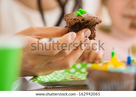 Closeup of woman's hand holding chocolate cupcake at birthday party - stock photo