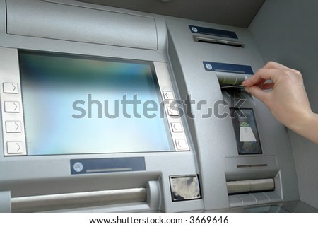 Closeup of woman's hand inserting e-card into ATM slot - stock photo