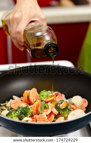 Closeup of woman's hand pouring olive oil over frozen vegetables in the frying pan - stock photo