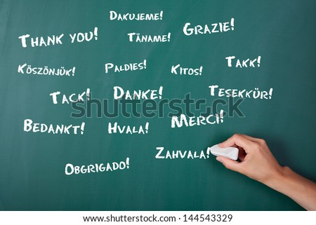 Closeup of woman's hand writing Thank You in various languages on chalkboard - stock photo