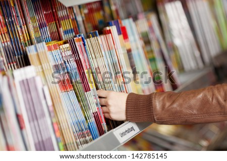 Closeup of woman's hands choosing magazines from shelf in supermarket - stock photo