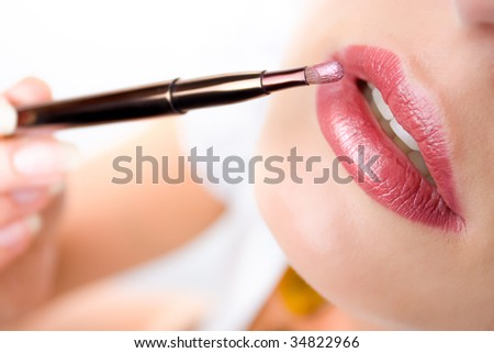 Closeup of woman's lips and  a brush with lipstick - stock photo