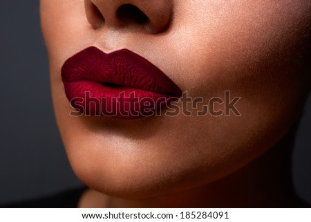 closeup of woman�¢??s sexy lips with red ombre style lipstick on tanned skin - stock photo