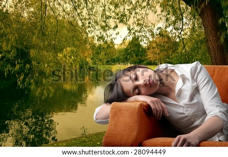 closeup of woman sleeping on armchair in a park - stock photo