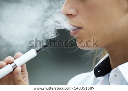 closeup of woman smoking e-cigarette and enjoying smoke. Copy space - stock photo