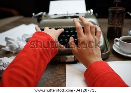 closeup of woman typing on old typewriter at table - stock photo