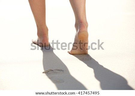 Closeup of woman walking on sandy beach leaving footprints in the sand