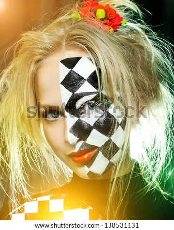 Closeup of woman with a chess pattern on her face - stock photo