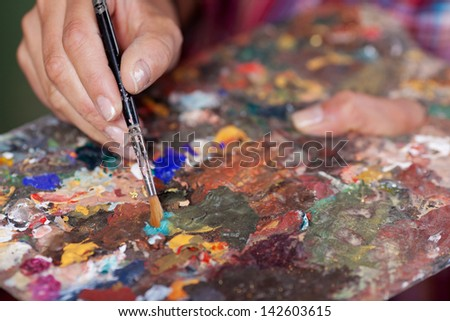 Closeup of womans hands mixing paint on palette at workshop - stock photo