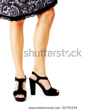 Closeup of womans legs and heels agasint a white background.