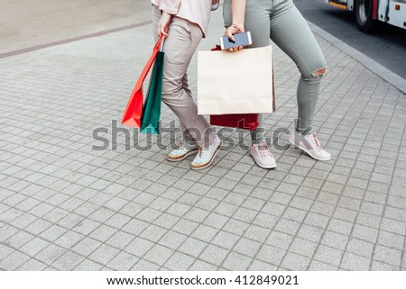 Closeup of women holding shopping bags on the street with copy space - stock photo
