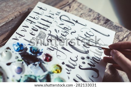 Closeup of women's hand drawing with watercolor on a wooden table. Soft focus photo of an artist during creation process.  - stock photo