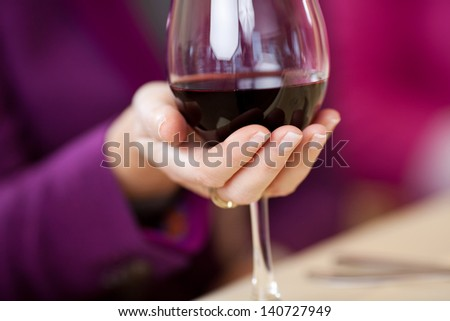 Closeup of women's hand holding wine glass at restaurant table - stock photo