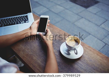 Closeup of women's hands holding cell telephone with empty copy space screen for your advertising text message or promotional content, female watching video on mobile phone during rest in coffee shop  - stock photo