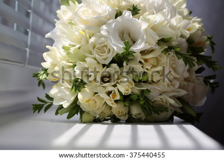 Closeup of wonderful elegant tender bridal bouquet of creamy tulips and roses flowers for marrying ceremony day natural beauty floral decor on white shadow background, horizontal picture  - stock photo