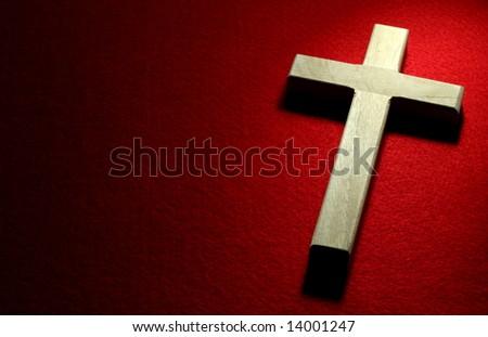 Closeup of wood crucifix on red felt background. - stock photo