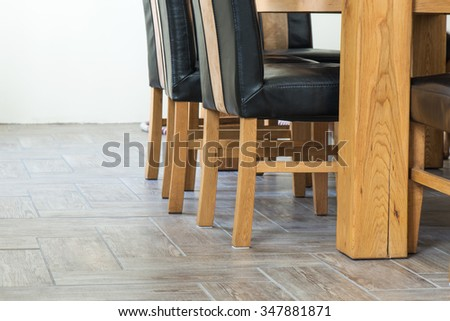 Closeup of wooden chairs and table legs on ceramic tile floor during renovation  - stock photo