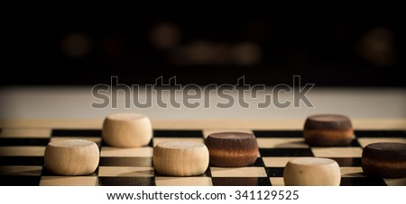 Closeup of wooden checkers on the board.