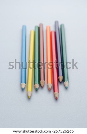Closeup of wooden colored crayons over blue background, shallow depth of field - stock photo