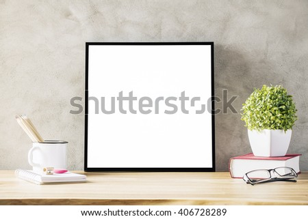 Closeup of wooden desk with blank frame, flowerpot, iron mug with pencils and glasses on concrete background. Mock up - stock photo