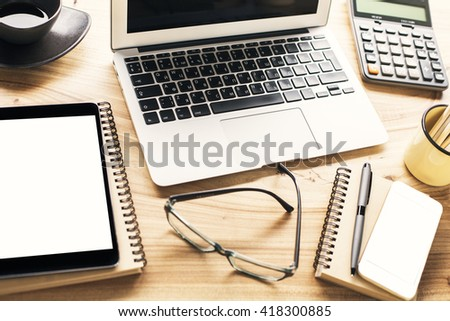 Closeup of wooden desktop with blank tablet, smartphone, laptop and other office tools. Mock up - stock photo