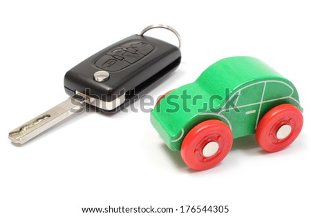 Closeup of wooden green toy car and car key, vehicle key. Isolated on white background - stock photo