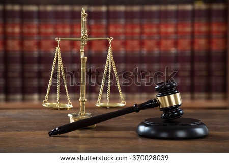 Closeup of wooden mallet and justice scale on table in courtroom