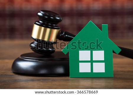 Closeup of wooden mallet with green paper house on table in courtroom - stock photo