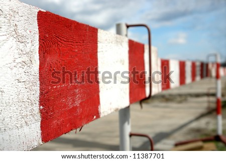 Closeup of wooden red and white striped road construction barriers - converging perspective - stock photo