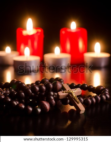 Closeup of wooden rosary on candlelight background - stock photo