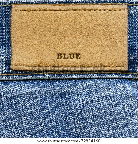 """Closeup of word """"BLUE"""" on blank grungy artificial leather label on worn blue denim, kind of a background - stock photo"""