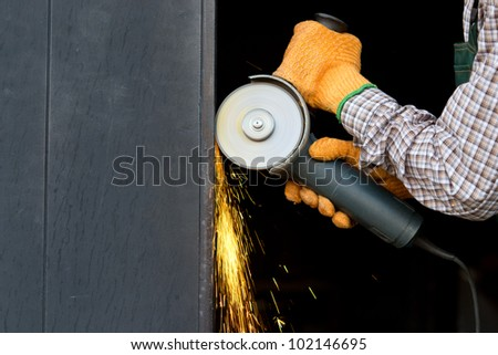Closeup of worker hands in orange gloves with angle grinder - stock photo